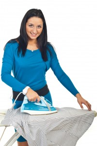 Smiling woman ironing a shirt